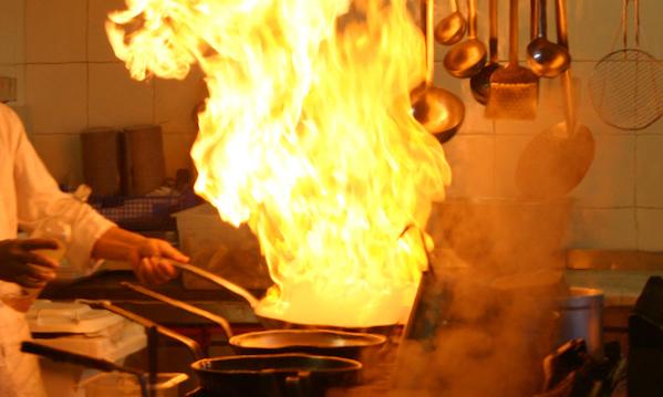 Piatto flambé al ristorante, fiamme su due persone